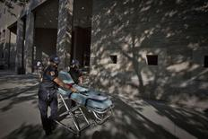 Медработники у больницы Mount Sinai в Нью-Йорке, где госпитализирован человек с симптомами лихорадки Эбола, 4 августа 2014 года. Надежды на создание лекарства против смертельно опасного вируса, вызывающего геморрагическую лихорадку Эбола, сегодня связаны с маленькой калифорнийской биотехнической компанией, чей экспериментальный препарат применяется для терапии двух американских медиков-миссионеров, подцепивших инфекцию в Африке. REUTERS/Carlo Allegri