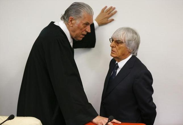 Formula One Chief Executive Bernie Ecclestone talks with hislawyer Sven Thomas (L) before the continuation of his trial at the regional court in Munich August 5, 2014. REUTERS/Michael Dalder