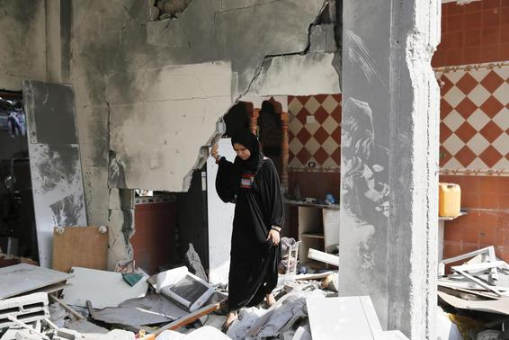 A Palestinian woman looks through her damaged home after returning to Beit Hanoun town, which witnesses said was heavily hit by Israeli shelling and air strikes during the Israeli offensive, in the northern Gaza Strip August 5, 2014.  REUTERS-Finbarr O'Reilly