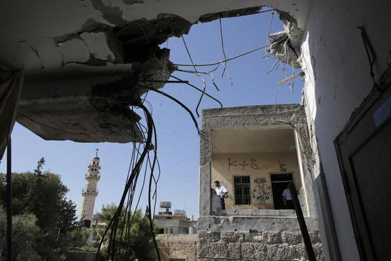 Palestinians inspect a damaged building after it was hit by mistake by a rocket fired from the Gaza Strip towards Israel by Palestinian militants, in the West Bank town of Beit Sahur near Bethlehem August 5, 2014. REUTERS-Ammar Awad
