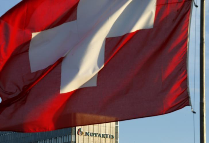 A national flag of Switzerland flies in front of a building of Swiss drugmaker Novartis in Basel January 29, 2014.  REUTERS/Arnd Wiegmann