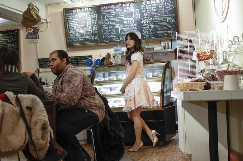 Reni Mimura, a waitress at the Maid Cafe New York, waits to greet a customer in New York November 20, 2013.  REUTERS/Shannon Stapleton