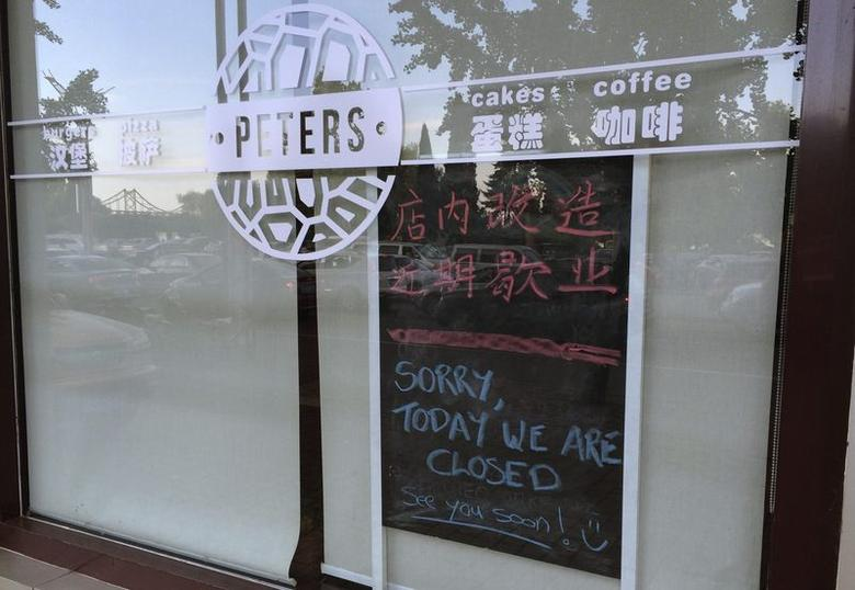 A notice indicating the closure of the shop is placed behind the window of the coffee shop owned by Canadian couple Kevin Garratt and Julia Dawn Garratt in Dandong, Liaoning province, August 5, 2014. REUTERS/Ben Blanchard
