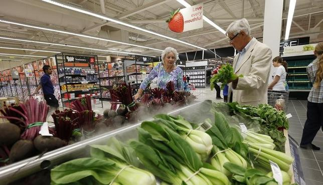Customers shop for vegetables at a Tesco Extra supermarket in Watford, north of London August 8, 2013. REUTERS/Suzanne Plunkett