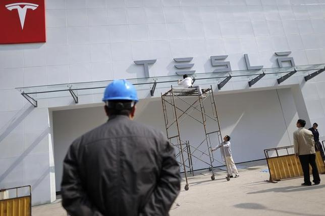 Labourers work on the exterior of a new Tesla showroom in Shanghai, April 22, 2014. REUTERS/Stringer