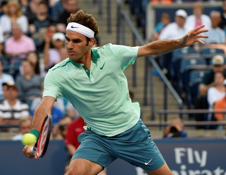 Aug 5, 2014; Toronto, Ontario Canada; Roger Federer of Switzerland plays a backhand dropshot against Peter Polanski of Canada on day two of the Rogers Cup tennis tournament at Rexall Centre. Mandatory Credit: Peter Llewellyn-USA TODAY Sports