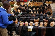A man prepares wigs as he waits for customers in downtown Johannesburg, August 5, 2014. REUTERS/Siphiwe Sibeko