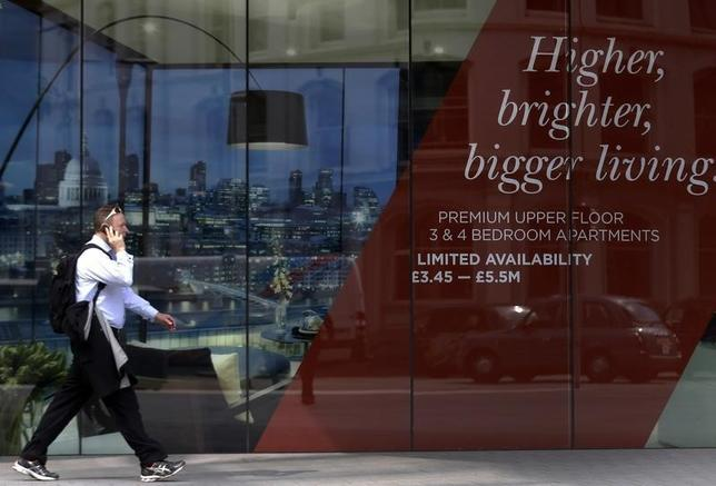 A man walks past the signage of a new property development advertising apartments for 5.5 million pounds sterling in central London July 2, 2014.  REUTERS/Luke MacGregor