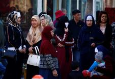 Uighur women stand next to a street to wait for a bus in downtown Urumqi, Xinjiang Uighur Autonomous Region May 1, 2014.   REUTERS/Petar Kujundzic