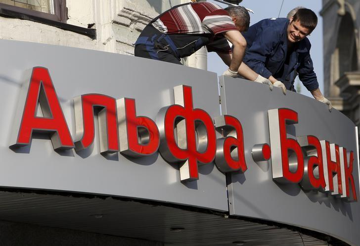 Workers install a signboard outside an Alfa-Bank office in central Moscow April 19, 2013. REUTERS/Sergei Karpukhin