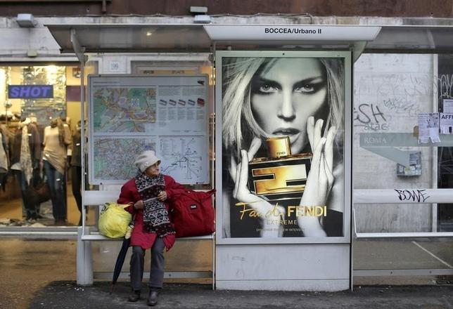 A woman waits at a bus stop in Rome, December 10, 2012.  REUTERS/Max Rossi