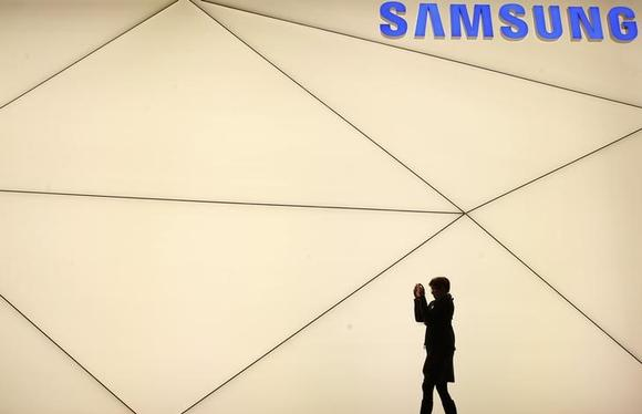 A woman takes a picture outside the Samsung stand at the Mobile World Congress in Barcelona February 24, 2014.  REUTERS/Albert Gea/Files