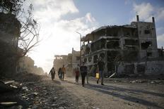 Palestinos caminham diante de prédios destruídos na Cidade de Gaza. 06/08/2014  REUTERS/Finbarr O'Reilly