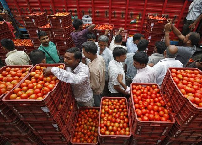 Customers crowd amid stacked baskets of tomatoes at a wholesale vegetable and fruit market in Chandigarh August 7, 2014.  REUTERS/Ajay Verma