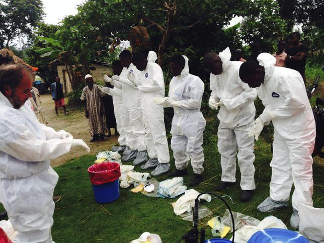 Volunteers prepare to remove the bodies of people who were suspected of contracting Ebola and died in the community in the village of Pendebu, north of Kenema August 2 , 2014. REUTERS/WHO/Tarik Jasarevic/Handout via Reuters
