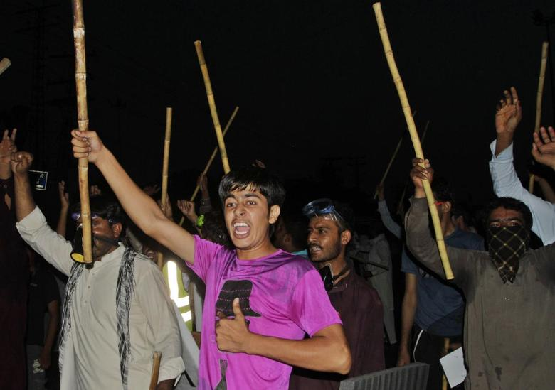 Supporters of Muhammad Tahirul Qadri, Sufi cleric and leader of political party Pakistan Awami Tehreek (PAT), chant slogans as they wave sticks during a protest in Lahore August 8, 2014.  REUTERS/Mohsin Raza