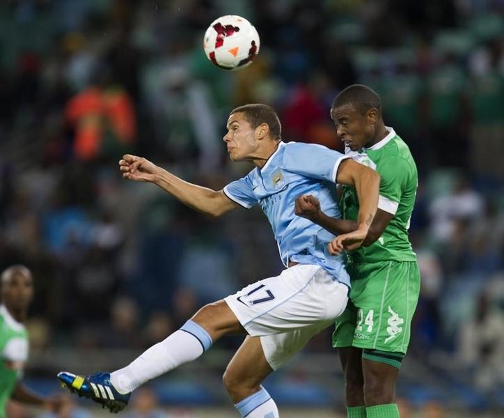 Manchester City's Jack Rodwell (L) and AmaZulu's Tamsanqa Teyise fight for the ball during the Nelson Mandela Invitational soccer match played on the birthday of the former South African President at the Moses Mabhida Stadium in Durban, July 18, 2013.  REUTERS/Rogan Ward