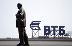 A sign for the logo of VTB Bank on the top of a building is pictured past a monument of Soviet state founder Vladimir Lenin in central Stavropol, southern Russia July 17, 2014. REUTERS/Eduard Korniyenko (RUSSIA - Tags: BUSINESS POLITICS LOGO CITYSCAPE)