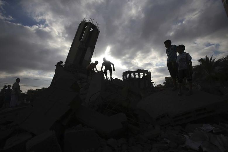 Palestinians stand atop the remains of a mosque, which witnesses said was destroyed in an Israeli air strike before a 72-hour truce, in Khan Younis in the southern Gaza Strip August 11, 2014. REUTERS/Ibraheem Abu Mustafa