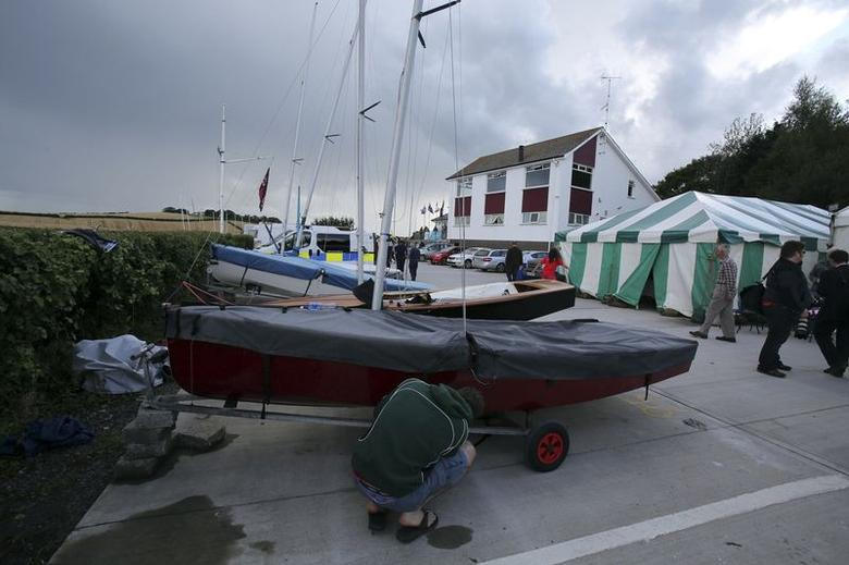 A man works on a dingy near the scene where the world championship race for GP14 class dinghies was held on Strangford Lough in County Down, Northern Ireland August 11, 2014. . REUTERS/Stringer