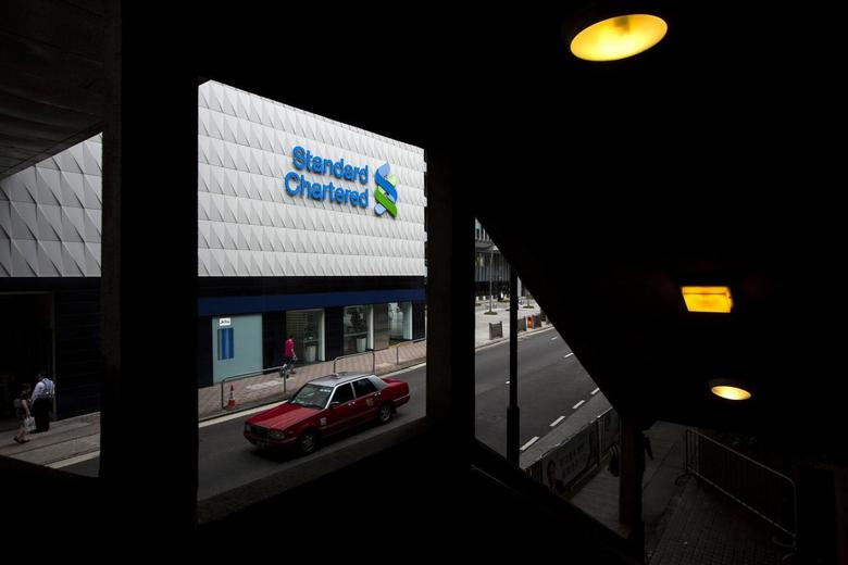 A taxi drives past Standard Chartered's main branch in Hong Kong August 6, 2014.  REUTERS/Tyrone Siu