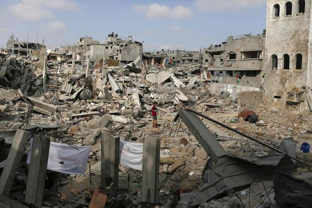 A boy stands amid the ruins of buildings that witnesses say were destroyed by Israeli air strikes in the Shejaia neighbourhood in Gaza City August 12, 2014. REUTERS/Siegfried Modola