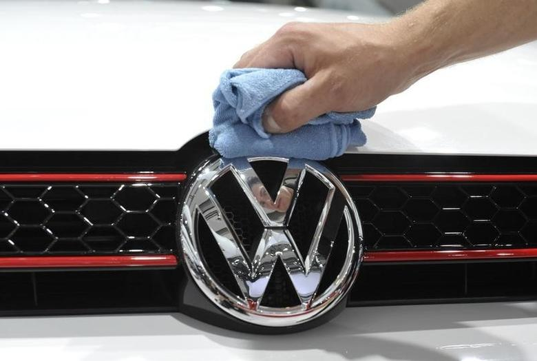 A man polishes the Volkswagen logo on a vehicle at an exhibition which is part of the annual shareholders meeting of Volkswagen AG in Hamburg April 23, 2009.    REUTERS/Morris Mac Matzen