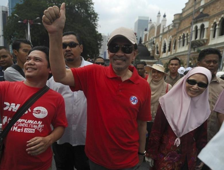 Malaysia opposition Anwar Ibrahim (C) and his wife Wan Azizah (R) walk to Independence Square during a protest against Goods and Services Tax (GST) in Kuala Lumpur May 1, 2014. REUTERS/Stringer