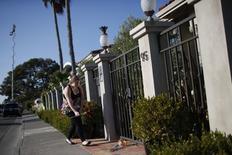 En la imagen, una mujer deja flores a las fueras de la casa del actor y comediante, Robin Williams, en Tiburon, California. 11 de agosto, 2014. En el barrio de Robin Williams en el norte de California, lejos de los focos y el glamour de Hollywood, una comunidad  entristecida y conmovida recuerda a un hombre sencillo al que le gustaba montar en bicicleta y que saludaba y se paraba a conversar con los vecinos.   REUTERS/Stephen Lam