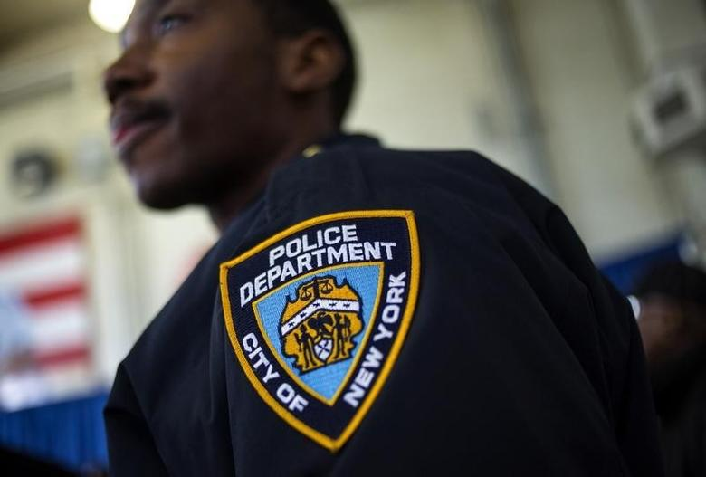 A New York Police Department officer is seen as Mayor Bill de Blasio attends a news conference in the Brownsville neighborhood in the borough of Brooklyn, New York January 30, 2014.  REUTERS/Eric Thayer