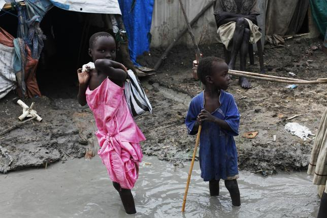 Children walk through mud in the internally displaced persons (IDP) camp inside the United Nations base in Malakal July 23, 2014.  REUTERS/Andreea Campeanu