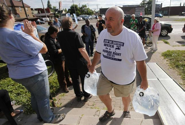 Canadian water activist Rob McGuffin delivers containers of water from Canada to the St. Peter's Episcopal church to protest against the increase in water shutoffs for residential customers with unpaid bills in Detroit, Michigan July 24, 2014.    REUTERS/Rebecca Cook