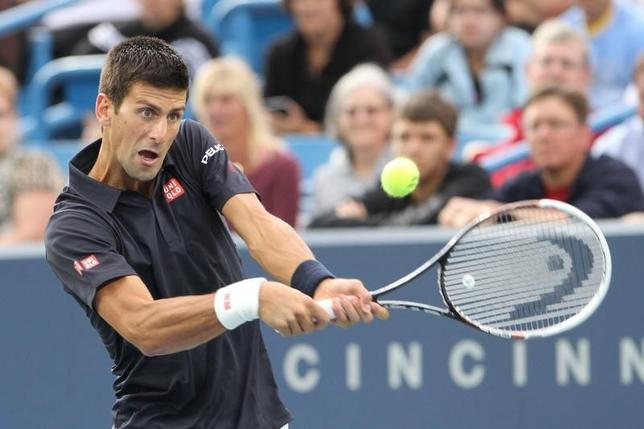 Aug 12, 2014; Cincinnati, OH, USA; Novak Djokovic returns the serve of Gilles Simon on day two of the Western and Southern Open tennis tournament at Linder Family Tennis Center. Mandatory Credit: Mark Zerof-USA TODAY Sports