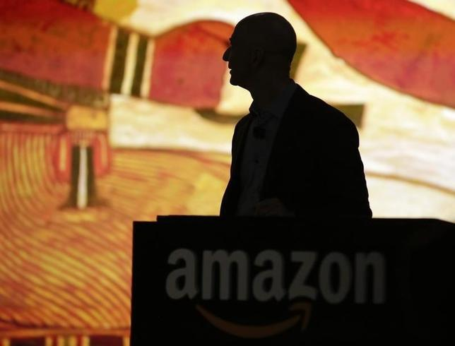 Amazon CEO Jeff Bezos is silhouetted during a presentation of his company's new Fire smartphone at a news conference in Seattle, Washington June 18, 2014. REUTERS/Jason Redmond