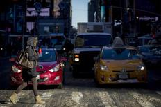 Cars wait at a stoplight a morning commuter crosses the street in Times Square in Manhattan in New York January 22, 2014.  REUTERS/Brendan McDermid
