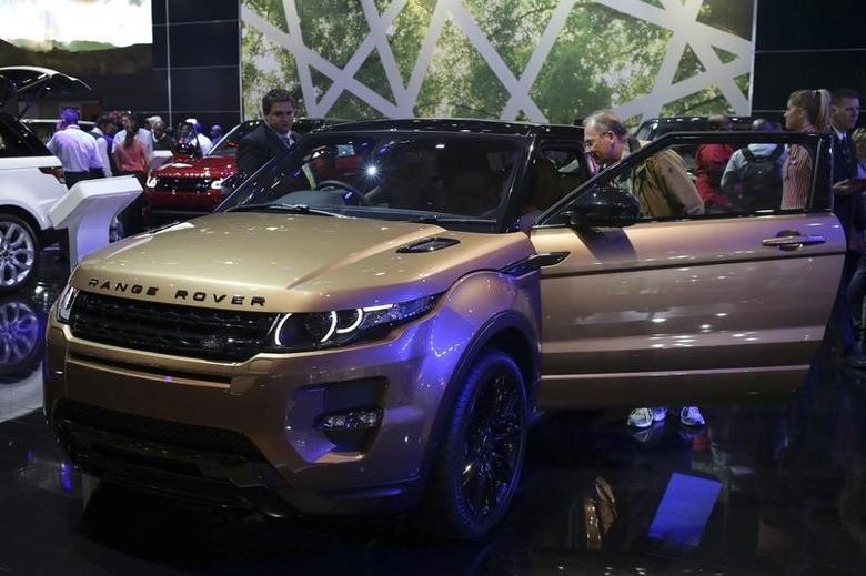 A visitor stands next to the Range Rover Evoque during a media preview day of the Johannesburg International Motor Show, October 17, 2013. REUTERS/Siphiwe Sibeko