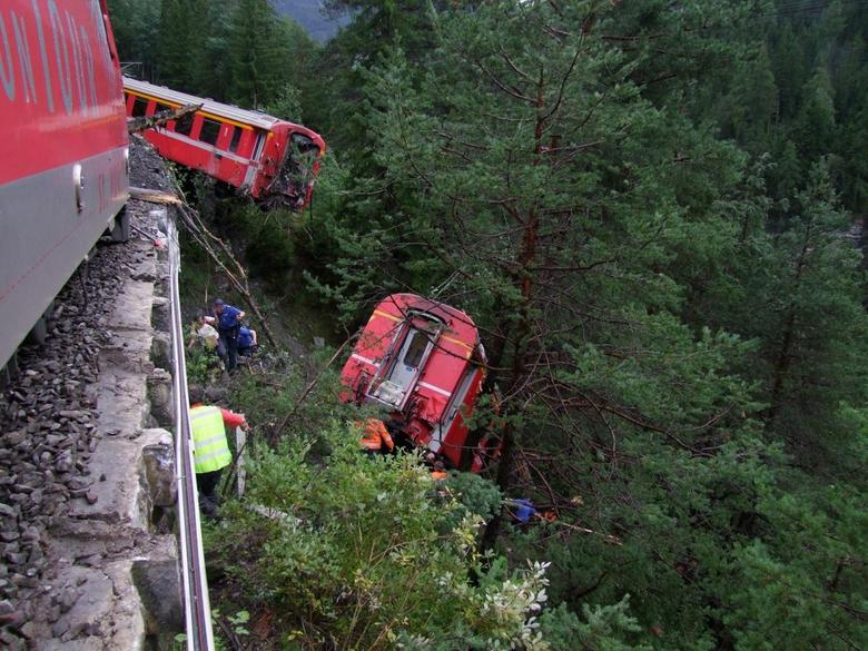 Police and rescue workers help after a passenger train derailed into a ravine near Tiefencastel in a mountainous region of southeastern Switzerland after encountering a mudslide on the tracks August 13, 2014. REUTERS/Kantonspolizei Graubunden/Handout via Reuters