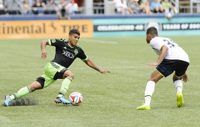 Jul 19, 2014; Seattle, WA, USA; Seattle Sounders FC defender DeAndre Yedlin (17) dribbles the ball while being defended by Tottenham Hotspur defender Ezekiel Fryers (35) during he second half at CenturyLink Field. Steven Bisig-USA TODAY Sports