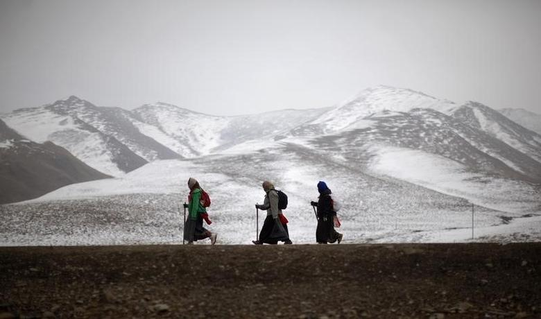 Ethnic Tibetan pilgrims walk on a road during Tibetan New Year in Langmusixiang, Sichuan Province February 22, 2012. REUTERS/Carlos Barria