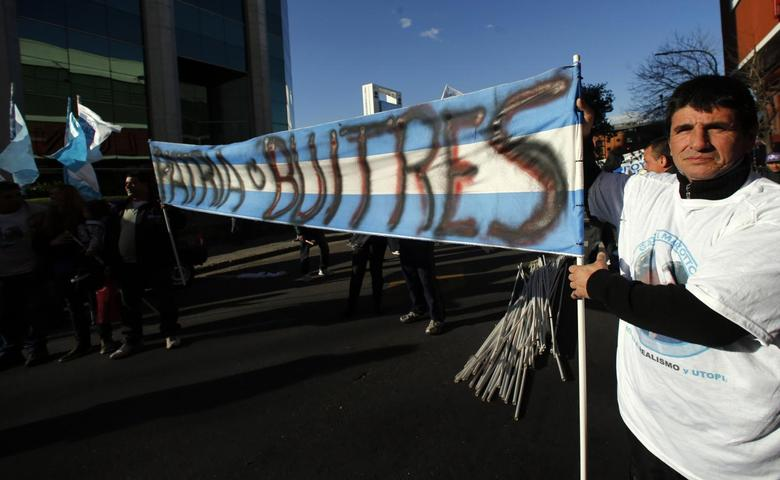Supporters of Argentina's government hold a sign that reads ''Homeland or vultures'' before a rally against the payment to what the government calls ''vulture'' creditors in Buenos Aires, August 12, 2014.   REUTERS/Marcos Brindicci