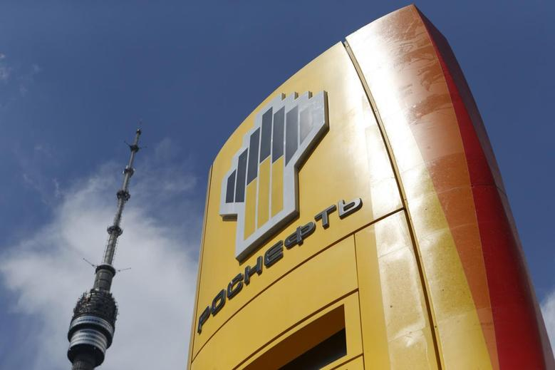 The logo of Russia's top crude producer Rosneft is seen on a price information board of a gasoline station, with the Ostankino television and radio tower seen in the background, in Moscow July 17, 2014. REUTERS/Sergei Karpukhin