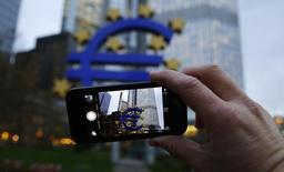 Homem usa telefone celular para tirar foto de escultura do euro do lado de fora do Banco Central Europeu, em Frankfurt. REUTERS/Kai Pfaffenbach