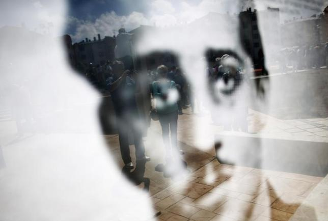 A man takes pictures as he is reflected in poster with of Gavrilo Princip before a ceremony in East Sarajevo, June 27, 2014.   REUTERS/Dado Ruvic