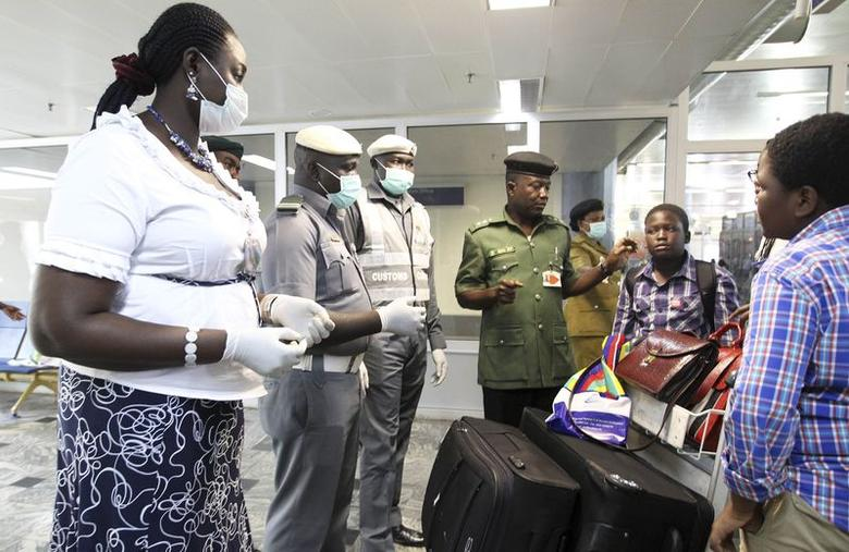 Nigerian custom officers wearing face masks and gloves screen passengers arriving at Nnamdi Azikiwe International Airport in Abuja August 11, 2014. REUTERS/Afolabi Sotunde