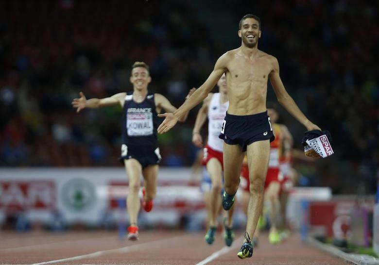 Mahiedine Mekhissi-Benabbad of France crosses the finish line with his vest in his hand, to win the men's 3000 metres steeplechase final during the European Athletics Championships at the Letzigrund Stadium in Zurich August 14, 2014.                     REUTERS/Arnd Wiegmann