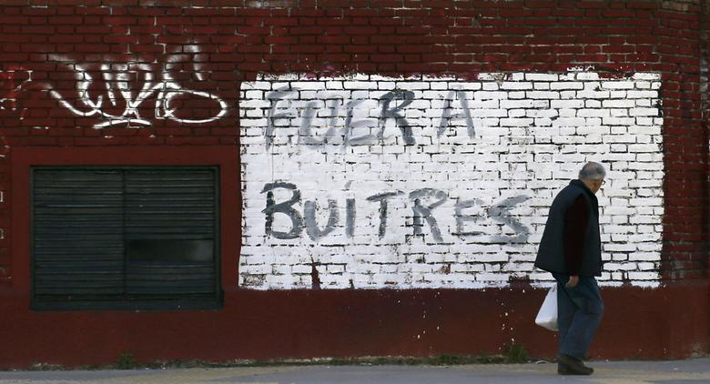 A man walks past a graffiti that reads, ''Get out vultures'' (the Argentine government derides the holdout funds as ''vultures'') in Buenos Aires, August 14, 2014. REUTERS/Marcos Brindicci