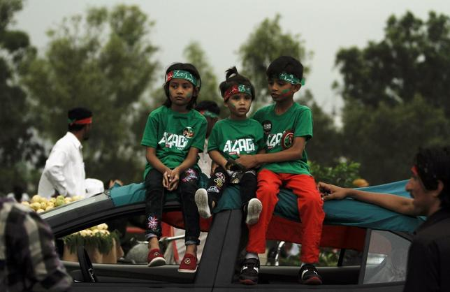 Supporters of cricketer-turned-opposition politician Imran Khan sit on the roof of a car as they wait with others to welcome Khan's Freedom March in Islamabad August 15, 2014. REUTERS/Faisal Mahmood