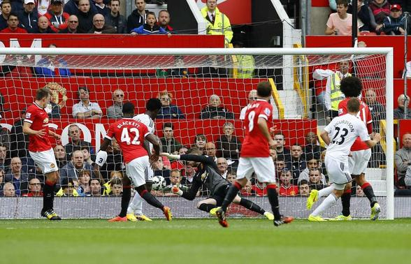 Swansea City's Gylfi Sigurdsson (R) scores a goal against Manchester United during their English Premier League soccer match at Old Trafford in Manchester, northern England August 16, 2014. REUTERS/Darren Staples