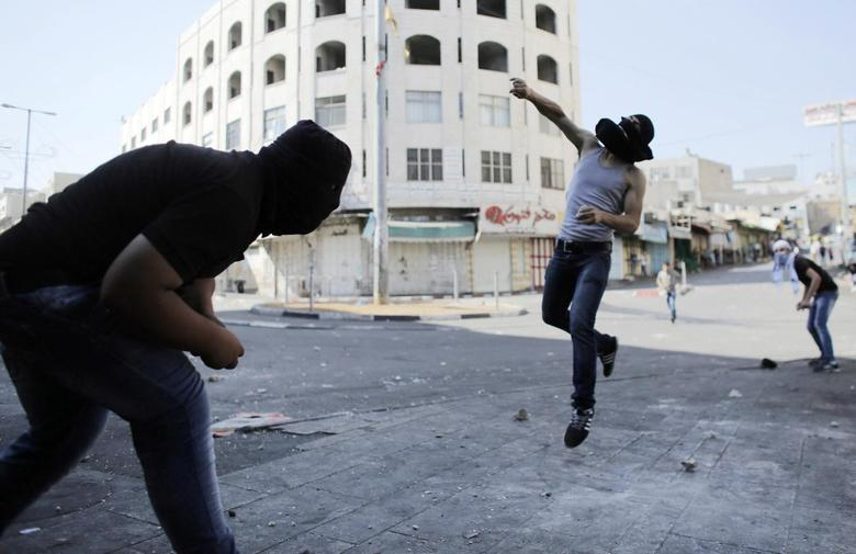 A Palestinian protester hurls a stone at Israeli troops following a demonstration against Israeli military action in Gaza, in the West Bank City of Hebron August 15, 2014.  REUTERS/Ammar Awad