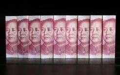 Банкноты в 100 юаней в Пекине 11 июля 2013 года. Прямые иностранные инвестиции (FDI) в Китай сократились впервые за 17 месяцев в январе-июле 2014 года из-за снижения вложений в производственный сектор страны из Японии, Европы и США. REUTERS/Jason Lee